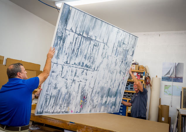 moving the finished custom framing project out of the workroom | Aldecor Custom Framing & Gallery - Naples, Florida
